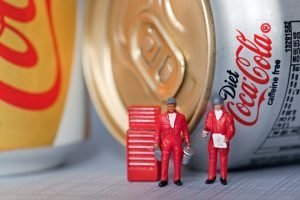 Two miniature workmen figurines with a toolbox in front of aluminium cans