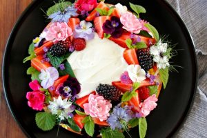 Homemade cake covered in edible flowers, herbs, and berries