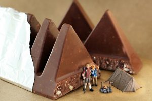 Miniature figurines camping by chocolate mountains of a Toblerone bar